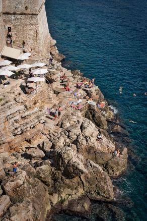 A Croatian beach below the walls of Dubrovnik .